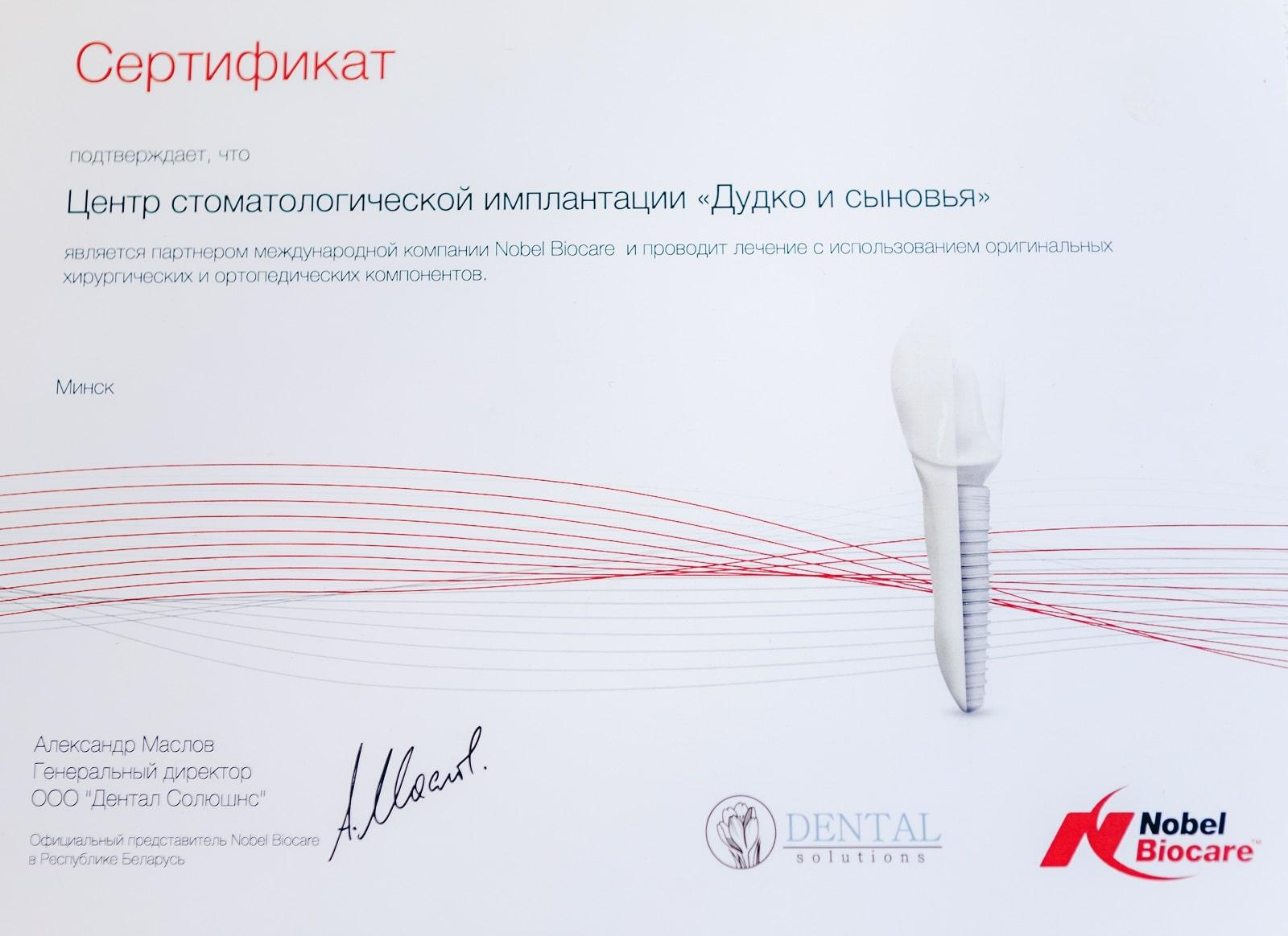 A certificate confirming that Dudko & Sons dentistry is a partner of the international company Nobel Biocare and performs operations using original surgical and orthopedic components. Signed by Alexander Maslov, General Director of Dental Solutions LLC.